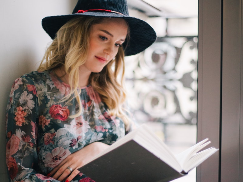 mladá žena číta knihu na okne